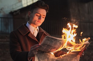 man-reading-burning-newspaper 200